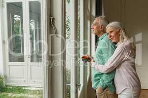 Active senior woman embracing senior man near door