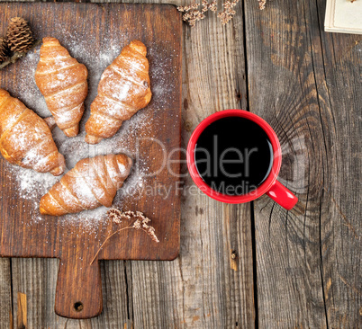 ceramic red cup with black coffee and wooden cutting board with
