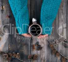female hands in a green knitted sweater holding a ceramic mug wi