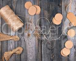 coil of brown rope, paper tags on a gray wooden background