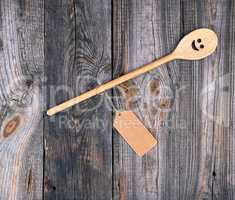wooden spoon with embedded eyes and a smile, empty brown paper t