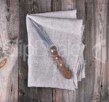 old kitchen knife on a gray napkin, wooden background