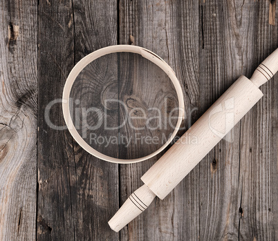 wooden rolling pin and a wooden round sieve on a gray table