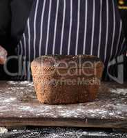 baked rye bread on a brown wooden board