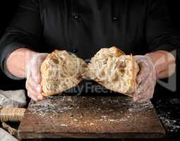 baker in black uniform broke in half a whole baked loaf of white