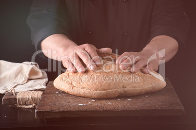male hands are holding brown baked rye bread over wooden board