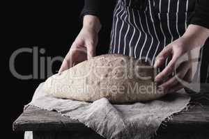 female hands holding oval baked wheat flour bread over wooden ta