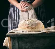 woman in an apron holds a gray linen napkin and round bread