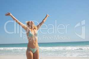 Woman in bikini with arm stretched out standing on the beach