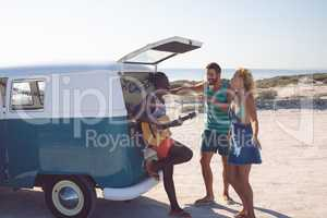 Group of friends having fun together near camper van at beach