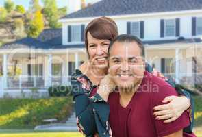 Mixed Race Young Adult Couple Portrait In Front of Beautiful House