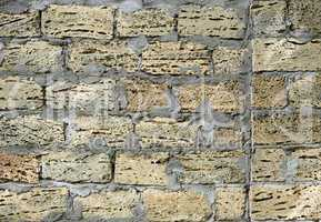 brick wall of large stone blocks fastened with gray cement