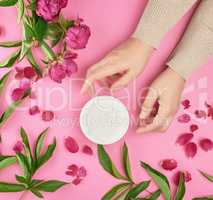 hands of a young girl with smooth skin and a jar with thick crea