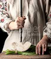 woman in a gray dress is cutting leaves of fresh sorrel