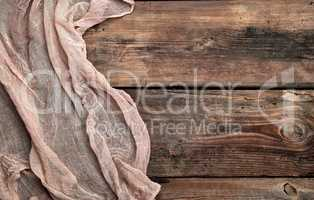gray textile napkin, brown wooden background