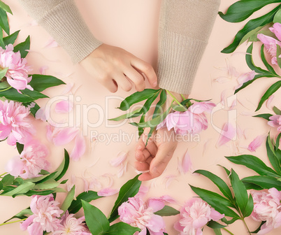 hands of a young girl with smooth skin and a bouquet of pink peo