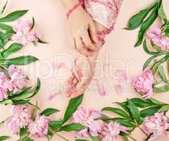 hands of a young girl with smooth skin and a bouquet of peonies