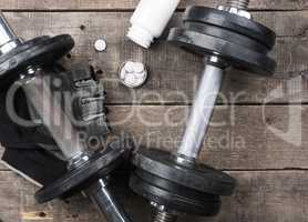 Protein pills with dumbbells on wood, top view