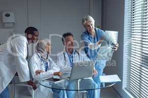 Medical team discussing over x-ray report in hospital