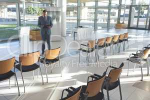 Caucasian businessman standing in conference room with digital tablet