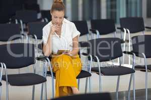 Caucasian female executive looking at digital tablet while sitting on chair in empty conference room