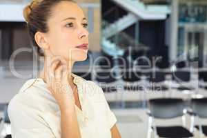 Caucasian female executive looking away while standing in empty conference room