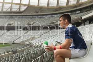 Caucasian male rugby player sitting with rugby ball in stadium