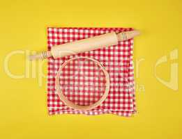 new wooden rolling pin on a red textile napkin and a round sieve