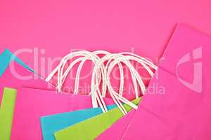 many rectangular multi-colored paper shopping bags with white ha
