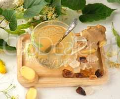 transparent cup with tea from ginger  and linden on a white wood