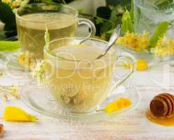 transparent cup with tea from linden on a white wooden board