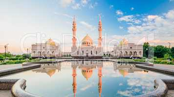 Beautiful White Mosque with Reflection  on Water at Sunset Light