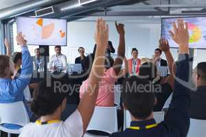 Audience raising their hands in a business conference