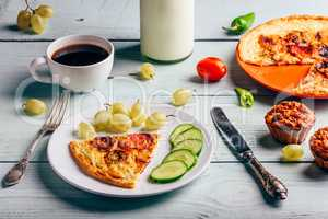 Frittata with with cup of coffee, grapes and muffins.