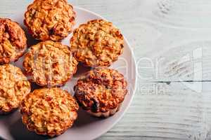 Cooked oatmeal muffins on white plate.