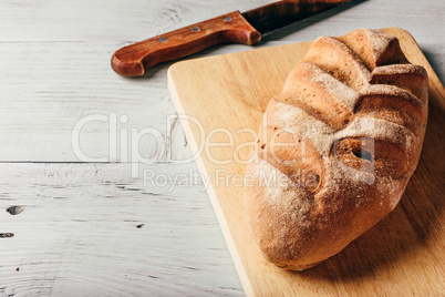 Rye loaf on cutting board with knife.