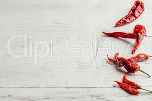 Dried chili peppers over wooden background