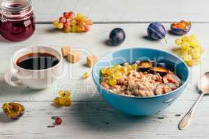 Porridge with plum, grapes and cup of coffee