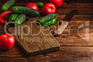 Cucumbers, tomatoes and chili peppers over wooden background.
