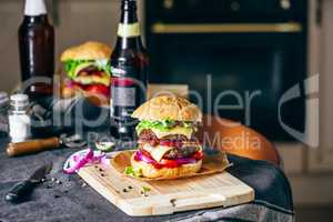 Burger on Cutting Board with  Bottle of Beer.