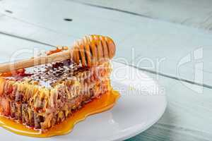 Honeycomb on plate with honey dipper