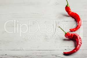 Chili peppers over light background.