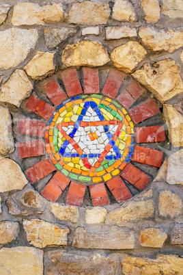 Mosaic star of David on stone wall.