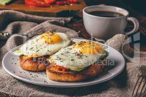 Italian toasts with vegetables and fried eggs on white plate and