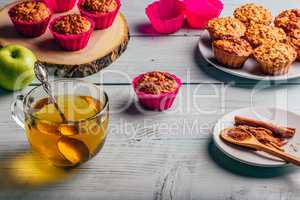 Cooked muffins with apple and cup of tea.