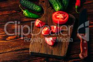 Sliced tomatoes on cutting board and cucumbers with chili pepper
