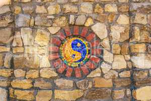 Mosaic symbol of Yin and yang on stone wall.