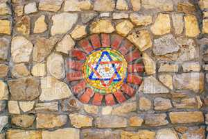 Mosaic star of David on stone wall.