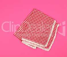 folded red kitchen towel in a cage on a pink background