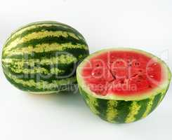 half ripe watermelon with red juicy pulp and seeds and a whole g